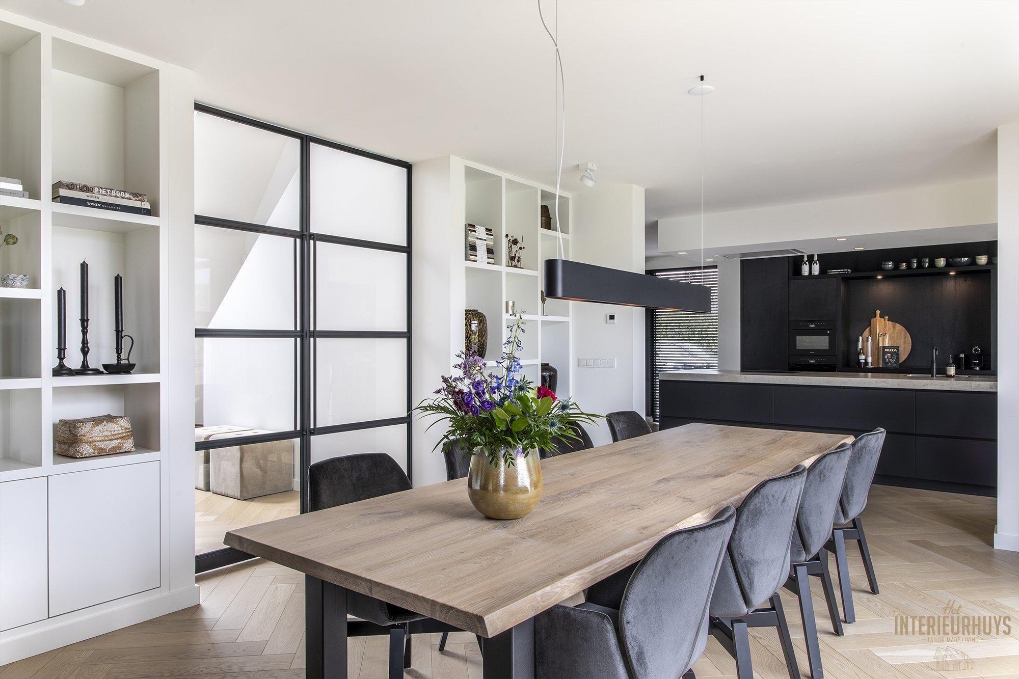 Eetkamer met op achtergrond keuken met kookeiland in de stijl klassiek modern.